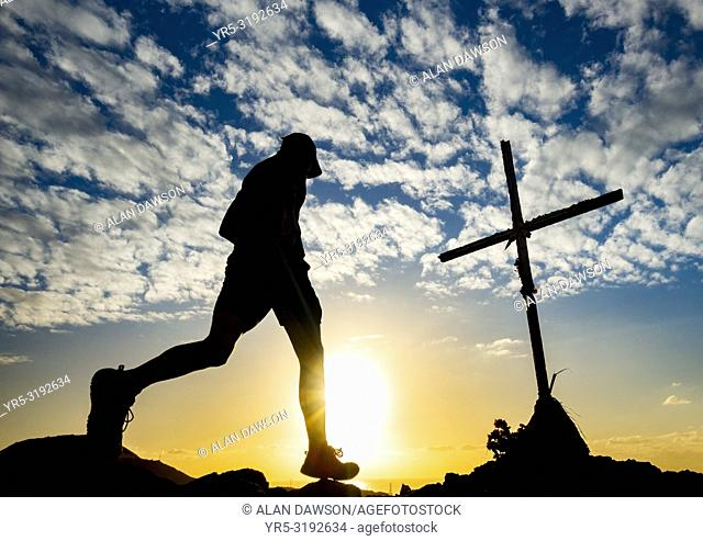 60 year old trail runner on mountain overlooking Las Palmas city on Gran Canaria at sunrise. La Isleta, Las Palmas, Gran Canaria, Canary Islands, Spain