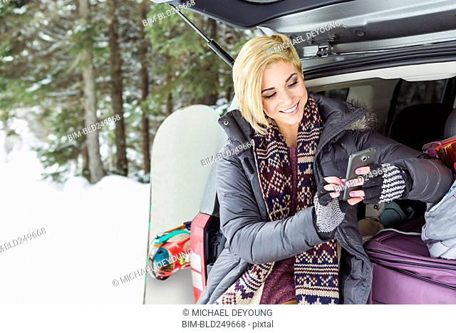 Caucasian woman at car texting on cell phone in winter
