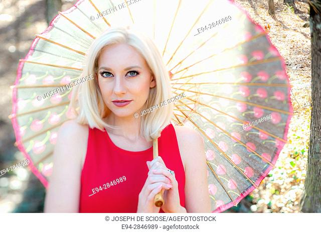 Portrait of a 30 year old blond woman looking at the camera and holding a parasol on her shoulder, outdoors