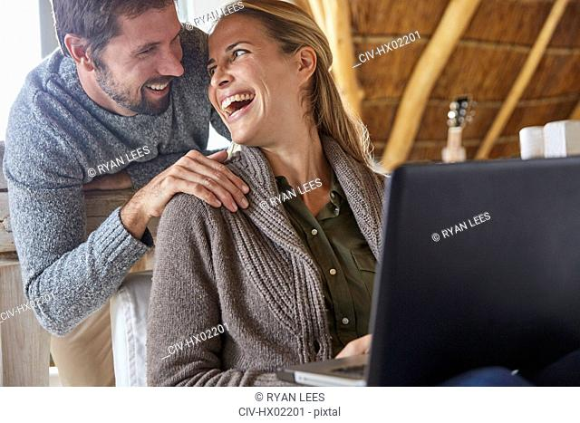 Happy couple laughing and using laptop