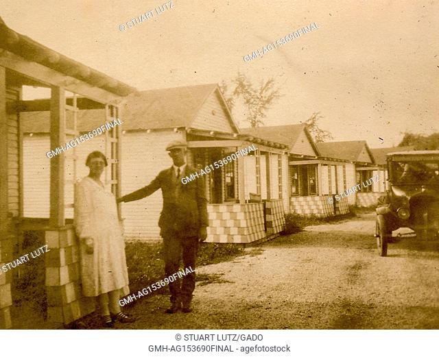 A man and woman, husband and wife, stand proudly beside a camping cabin, with their automobile in the background, during a road trip through New England