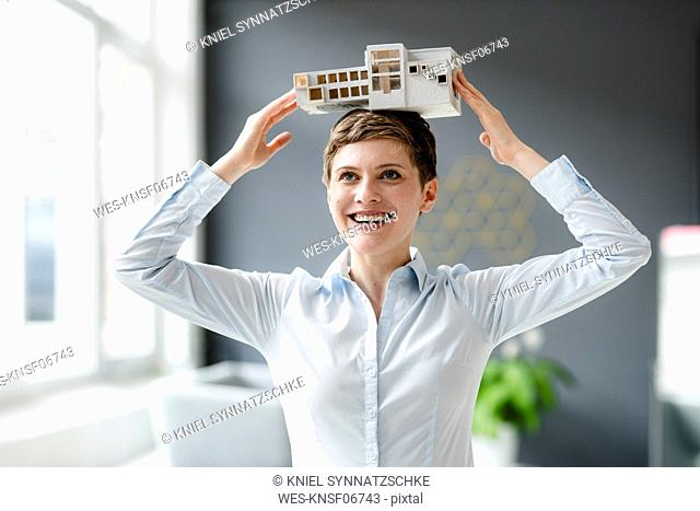 Happy businesswoman carrying architectural model on her head