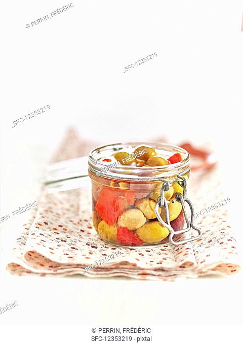 Lacto fermented green olives and red peppers in a mason jar