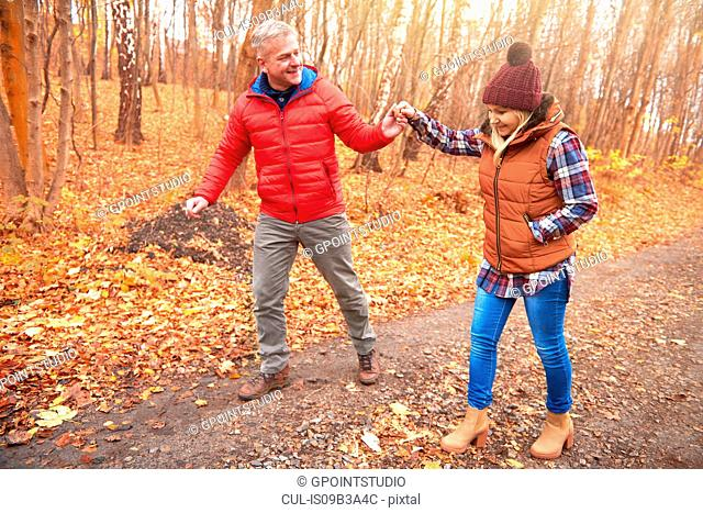 Mature couple walking along rural pathway, in autumn