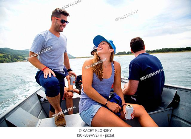Five adult friends drinking beer on fishing boat at Nehalem Bay, Oregon, USA