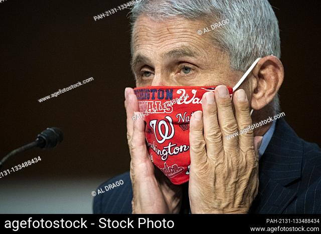 Anthony Fauci, director of the National Institute of Allergy and Infectious Diseases, adjusts a face covering during a Senate Health, Education