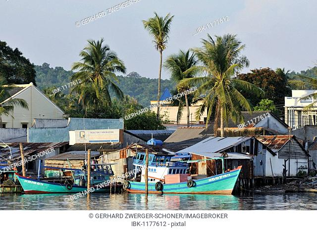 Fishing boats and quaint fishing village with simple colorful wooden houses and palm trees, Phu Quoc, Vietnam, Asia