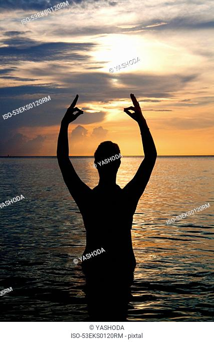 Silhouette of man meditating in water