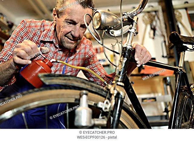 Senior man oiling bicycle in his workshop