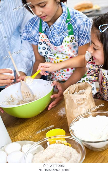 Girls baking with mother in kitchen