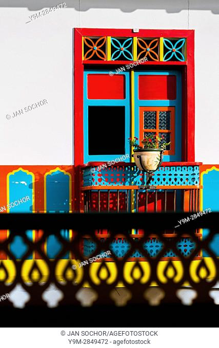A brightly painted wooden balcony is seen in the first floor of a colonial house in Jardín, a village in the coffee region (Zona cafetera) of Colombia