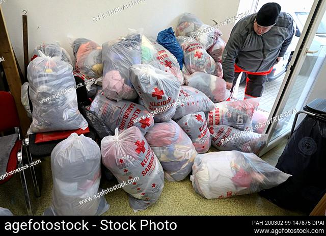 25 February 2020, Mecklenburg-Western Pomerania, Rostock: In the clothing store of the German Red Cross (DRK), clothing is delivered from used clothing...
