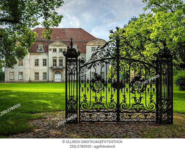 An old solitary wrought-iron locked gate in front of an abandoned baroque manor house in Mecklenburg-Pomerania, Germany, standing in a park environment