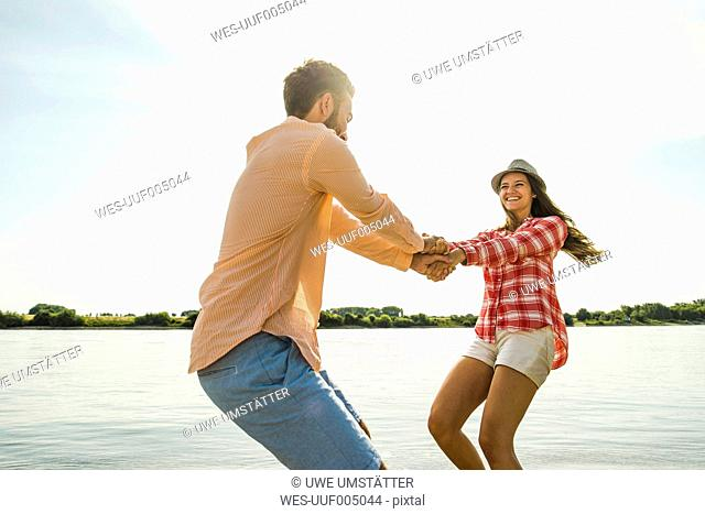 Carefree young couple hand in hand by the river