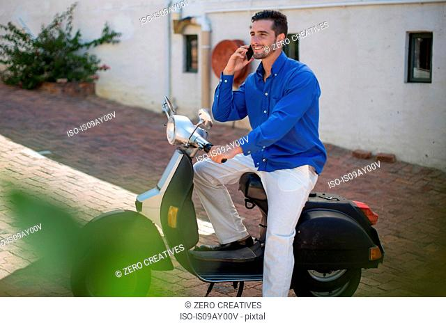 Young man on moped chatting on smartphone in city
