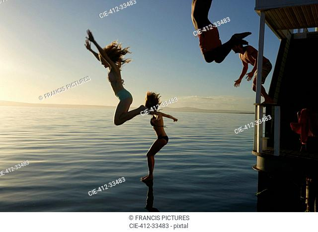 Young adult friends jumping from summer houseboat into sunset ocean
