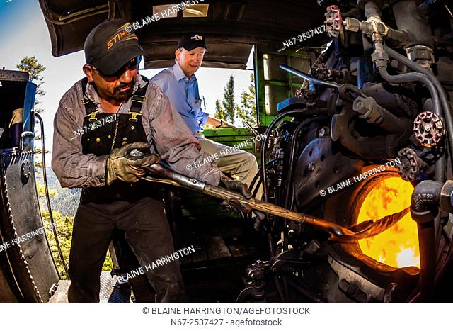 The fireman stokes the fire in the boiler of the steam engine (Colorado Governor John Hickenlooper sits behind), Cumbres & Toltec Scenic Railroad train on the...