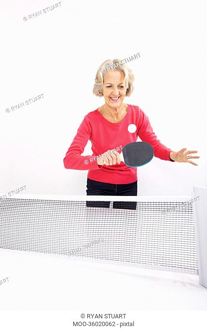 Happy senior woman playing table tennis
