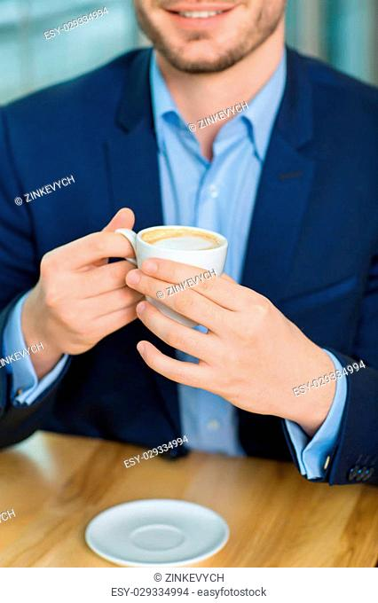 Close-up shot with selective focus of good-looking smiling man holding a cup of coffee