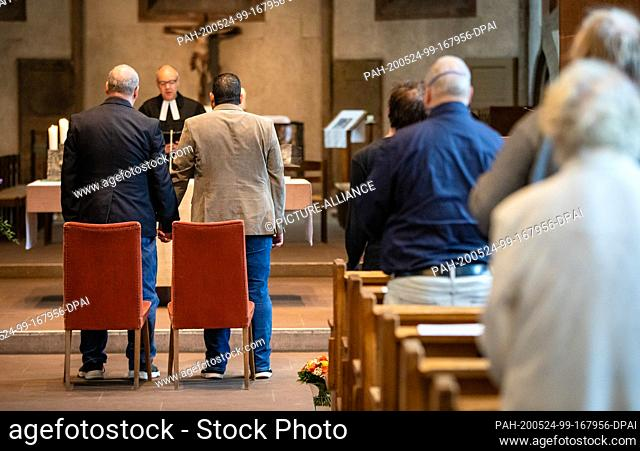 24 May 2020, Baden-Wuerttemberg, Stuttgart: Guests follow the blessing service of the homosexual couple Gerald (l) and Ahmad Wolf in the Leonard Church