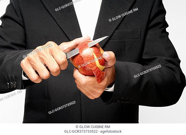 Mid section view of a waiter peeling an apple