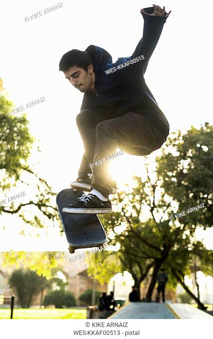 Young man with skateboard jumping in the air