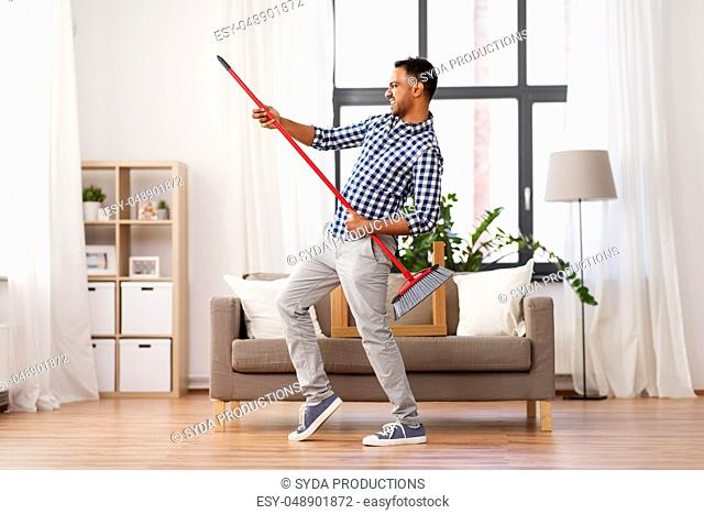 man with broom cleaning and having fun at home