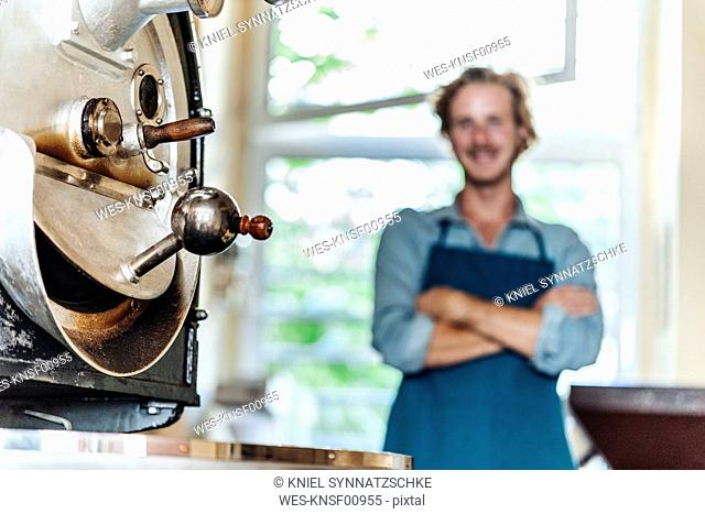 Machine and man in coffee roastery
