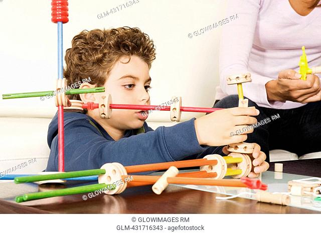 Woman assisting her son in assembling a toy