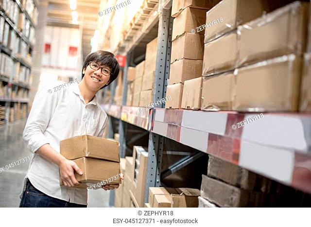 Young Asian man carrying paper box near product shelf in warehouse, shopping warehousing or working pick and packing concepts