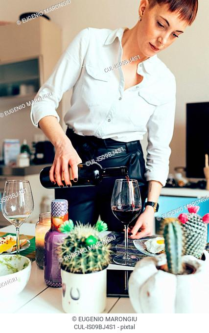 Woman pouring bottle of wine