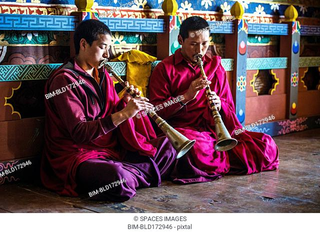 Asian monks playing instruments on temple floor