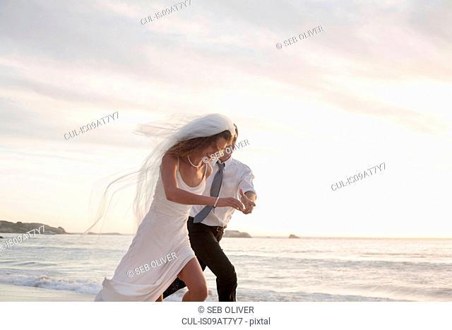 Bride and groom running along beach