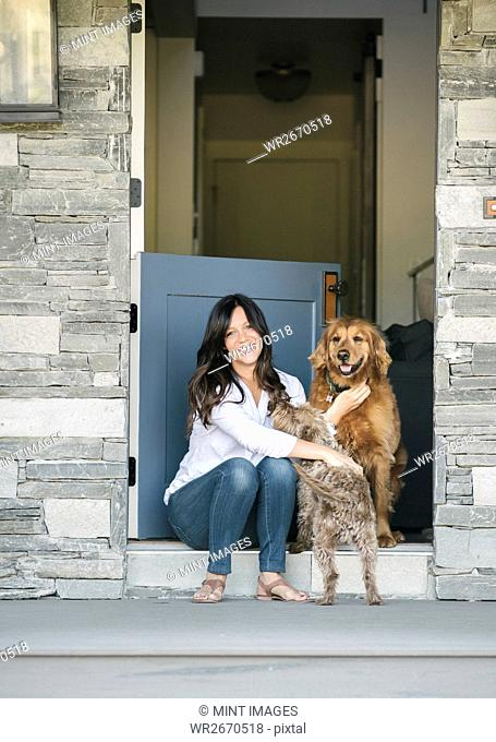 Woman sitting by her door patting her two dogs