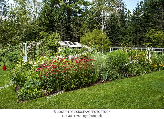 A perennial plant border in front of a fenced in vegetable garden