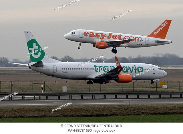 An easyJet aircraft (top) on its landing approach as a Transavia plane is waiting to be cleared for take-off in Schoenefeld, Germany, 06 March 2017