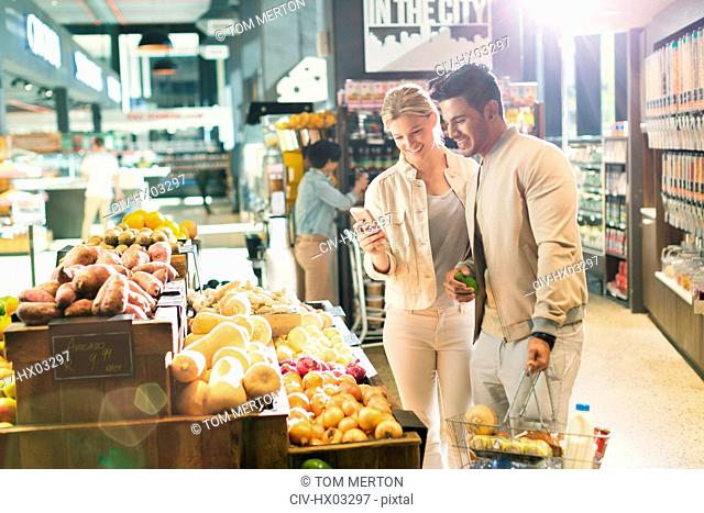 Young couple with cell phone grocery shopping at market