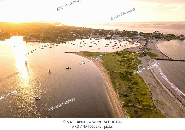 Early morning sun paints an orange glow over boats, mansions, and Napatree Point in Watch Hill, Westerly, Rhode Island