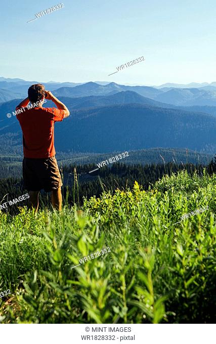 A man standing on a mountain ridge, taking a photograph of the landscape and forested valley