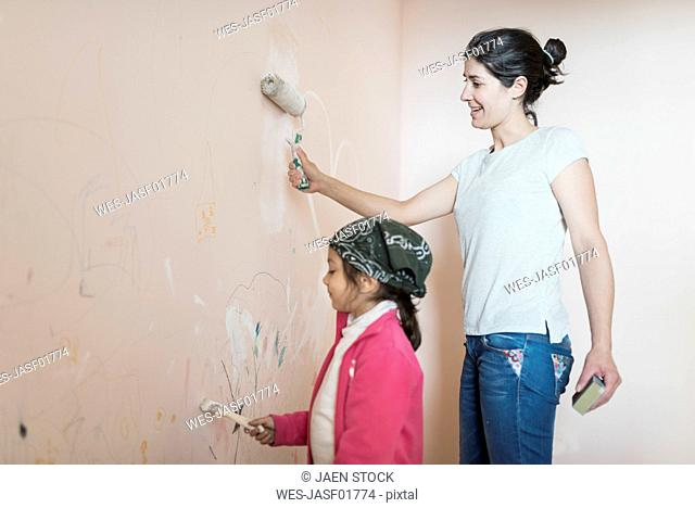 Mother and daughter painting wall in children's room