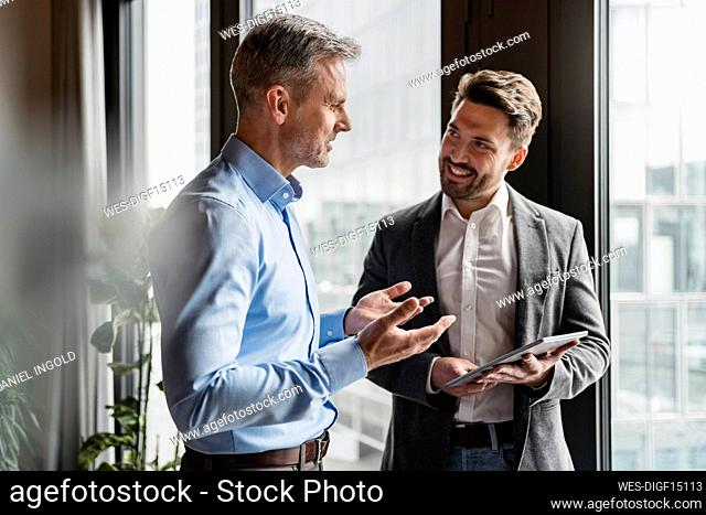 Male colleagues discussing in meeting at modern office