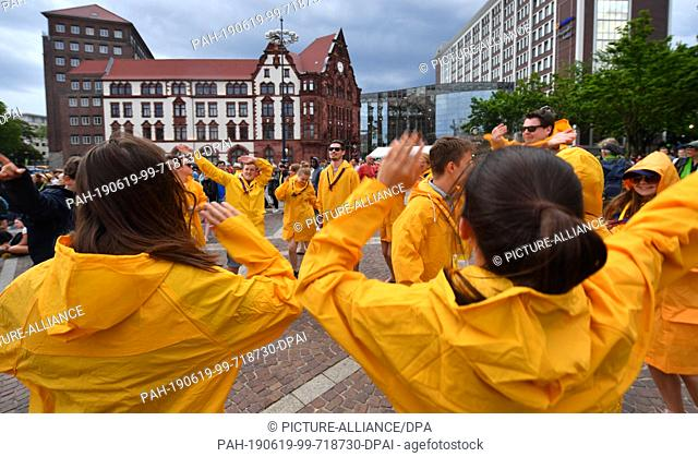 19 June 2019, North Rhine-Westphalia, Dortmund: Young participants dance in raincoats on stage at the opening event of the German Protestant Church Congress