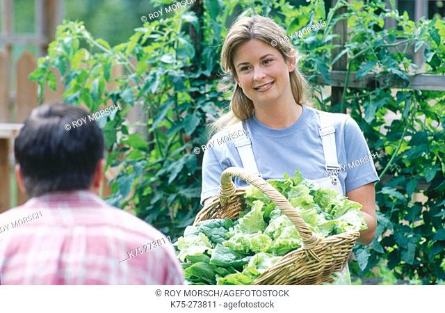 Woman showing off basket of greens