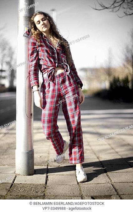 woman wearing pyjama, leaning on street lamp post in city