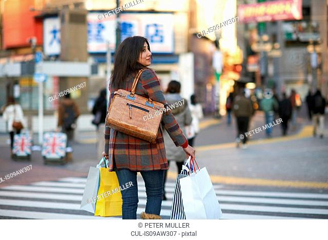 Rear view of mature woman in city carrying shopping bags crossing pedestrian crossing looking sideways, Shibuya, Tokyo, Japan