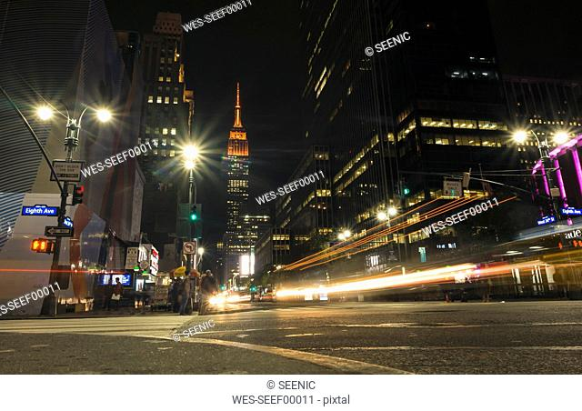 USA, New York City, Eighth Avenue and Empire State Building at night