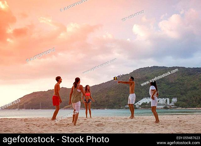Group of young people playing volleyball on beach at sunset
