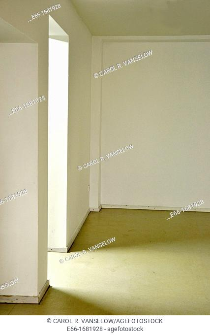 white corner with light streaming through doorway