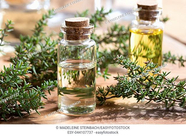 A bottle of thyme essential oil with fresh thyme leaves on a wooden background
