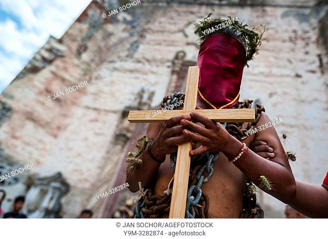 A chained penitent, wearing cactus spines stuck to his body and holding a wooden cross, takes part in the Holy week procession in Atlixco, Mexico, 30 March 2018